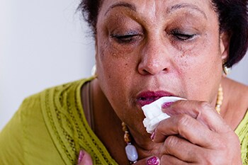 Lady experiencing  COPD  flare-up holding a handkerchief to her face